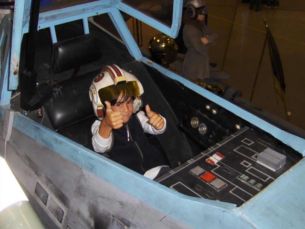 My son Parker at age 7, free to share his excitement to sit in a Star Wars X Wing.